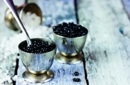 Black caviar in small round metal tin on ice. Selective focus