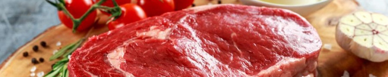 Fresh Raw Beef Steak Ribeye, with salt, peppercorns, rosemary, tomatoes and olive oil