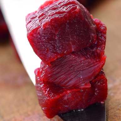 close up photography of three cubes of meat on a knife