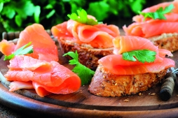 Delicious homemade smoked salmon gluten free canape garnished with a fresh parsley leaf on wood
