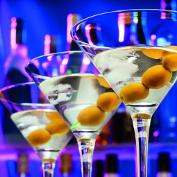 Martini glasses with olives with color lit bottles on background during happy hour